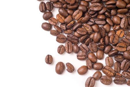 Roasted organic whole dark coffee beans, isolated on white background