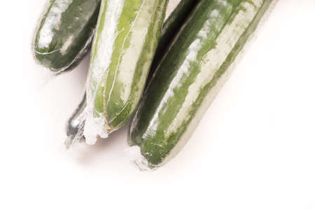 Bunch of cucumber wrapped in plastic films, isolated on white background Standard-Bild