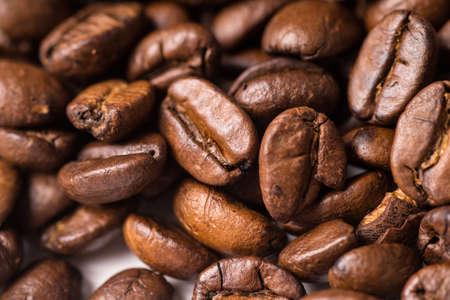 Roasted organic whole dark coffee beans, close up