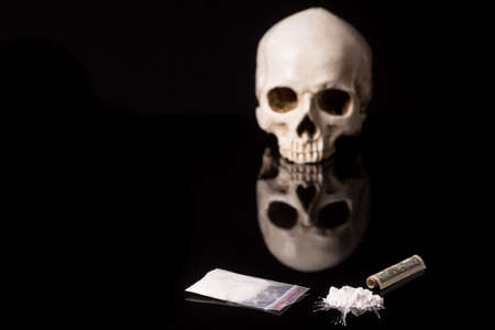cocaine, Herion or other illegal drugs that are sniffed by means of a tube or injected with a syringe, money and Skull, isolated on black glossy background Standard-Bild