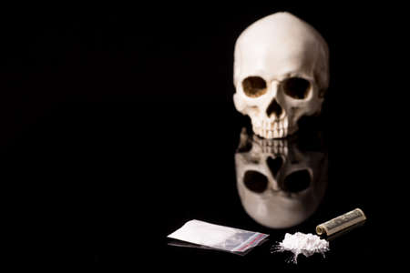 cocaine, Herion or other illegal drugs that are sniffed by means of a tube or injected with a syringe, money and Skull, isolated on black glossy background Standard-Bild - 133352204