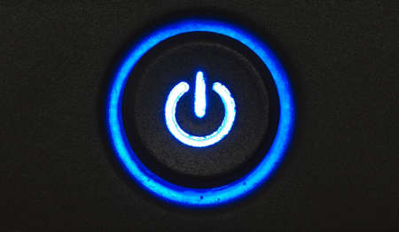 Blue glowing power button on a black pattern background