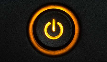 Brillant orange bouton d'alimentation de l'ordinateur sur un mod�le fond noir Banque d'images