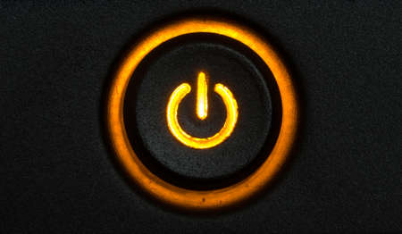 Orange glowing power button from computer on a black pattern background