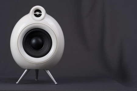 surround system: White speaker against grey background