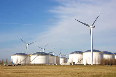 oil depot and storage tanks with wind turbine for clean energy Stock Photo