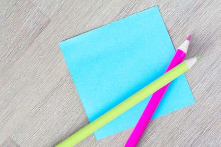 Blank blue Post-it note with colorful pencils
