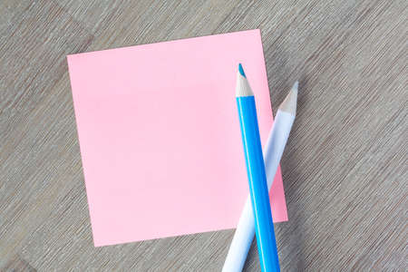 Blank pink post-it note with colorful pencils Stock Photo