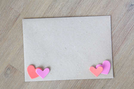 Natural envelope on a wooden background with hearts photo
