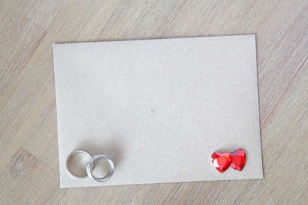 Natural envelope on a wooden background with hearts and a ring photo