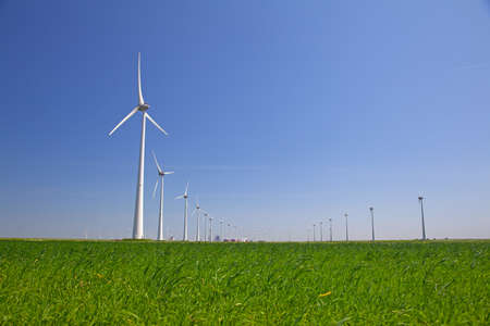 windturbines: Windturbines in a grassfield and a clear blue sky Stock Photo