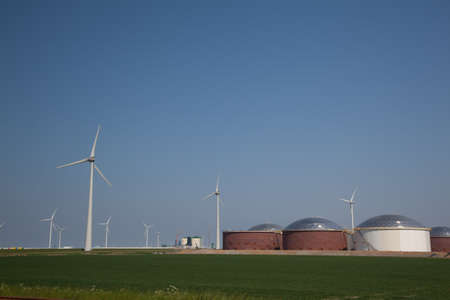 Windfarm with oiltanks and a clear blue sky Editorial