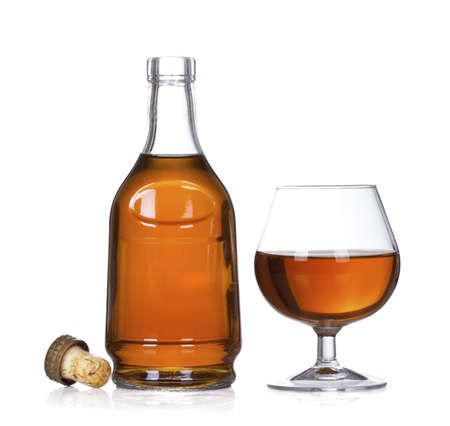Cognac brandy bottle and glass isolated on white background photo