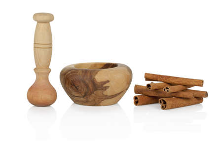 barbarum: Cinnamon with mortar and pestle isolated on white background Stock Photo
