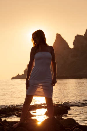 Beautiful lady standing by the sea at dawn