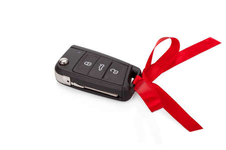 Gift idea: car keys with red ribbon isolated on white  photo