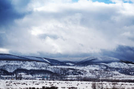 Winter cloudy day with hills in snow photo