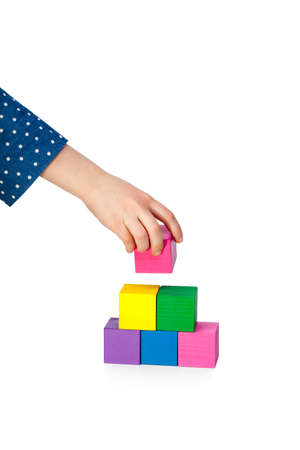 Childs hand building a brick tower isolated on white background photo