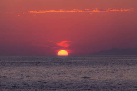 Amazing clowdy red dawn over sea photo