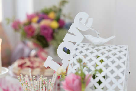 Romantic love sign on a cage with dove and bouquet flowers on background photo