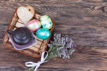 Colorful decorated Easter Eggs wirh flowers and teapot on wooden background