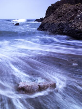 Long exposure of a receding wave around a rock on the beach as the next wave approaches, water with shades of dark blue due to the proximity of a storm. Imagens
