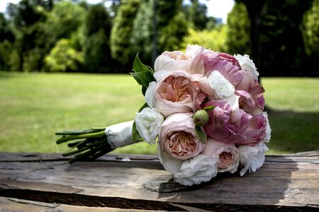 bridal bouquet in pink and white on an old piece of wood and a background of an unfocused field, image with selective focus to give prominence to the main subject. Stock Photo