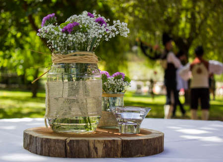 decorative motif composed of a floral motif in a glass container and on a piece of wood in an outdoor celebration, unfocused background to give more prominence to the motif