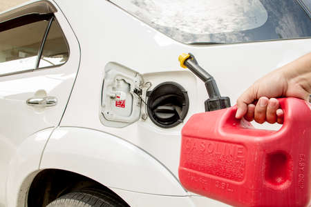 refilling: Man refilling the car with  Red gasoline Canister Stock Photo
