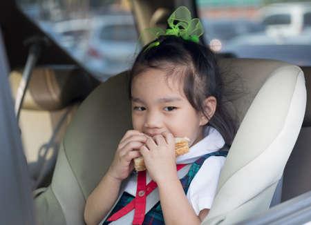 ni�a comiendo: ni�os en un coche que comen el desayuno antes de la escuela Foto de archivo