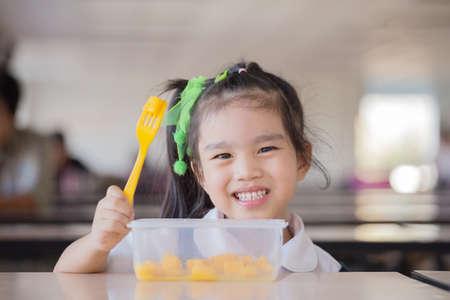 niños comiendo: La alimentación saludable - niño que come una fruta, un montón de fruta fresca en la mesa delante como después de la escuela