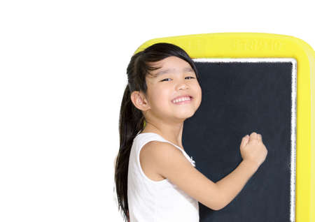smart little girl smiling in front of a blackboard  on white background Stock Photo