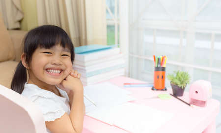 learning by doing: Happy little girl and early education. little kids doing his homework for fun and learning