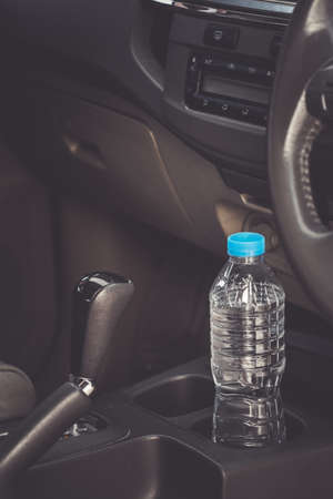 image concept Bottled water was left in the car for a long time. To drink it? Foto de archivo