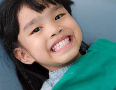 Pequeños dientes del paciente de la niña en blanco en el consultorio del dentista