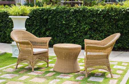 Wicker patio chairs and table in garden Foto de archivo