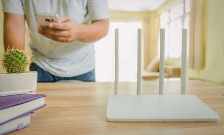 closeup of a wireless router and a man using smartphone on living room at home ofiice Stockfoto