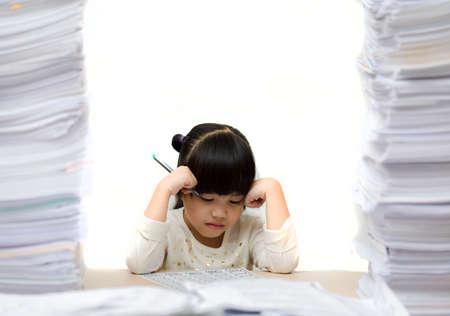 Little asian cute girl doing homework. big burden on students. overloaded child Foto de archivo