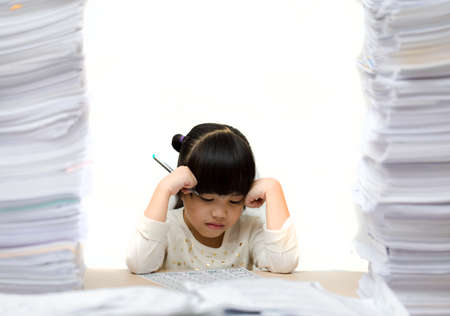 Little asian cute girl doing homework. big burden on students. overloaded child Stockfoto