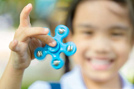 Happy child play with fidget spinner stress relieving toy in school