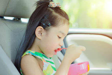 a young girl Eating breakfast on car