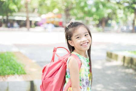 Menina asiática feliz que chega a escola de casa com uma mochila
