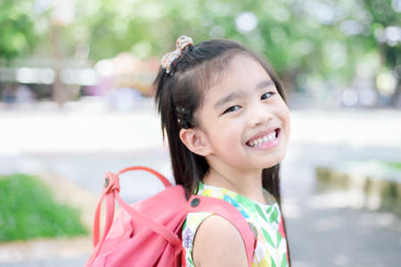 Happy asian girl arriving school from home with a backpack