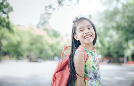 niños saliendo de la escuela: Happy asian girl arriving school from home with a backpack