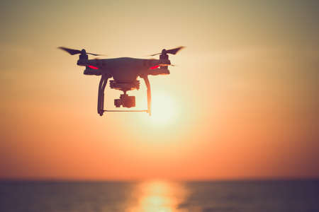 Silhouette of drone hovering in  beautiful sunset on the ocean. Stock Photo