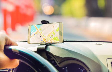 L'autista femminile che si siede nell'automobile usa lo Smart Phone mobile con l'applicazione di navigazione dei gps della mappa Archivio Fotografico