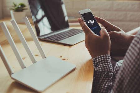 Joven usando móvil con conexión wifi en la pantalla. Las manos del hombre usando el dispositivo en la oficina en casa. Fondo borroso Foto de archivo