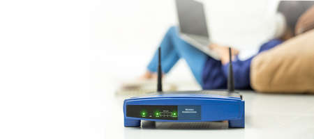 Wireless router and kids using a laptop in home. router wireless broadband home laptop computer phone wifi concept Standard-Bild