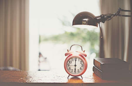Clock on wood in the morning, blurred bedroom background