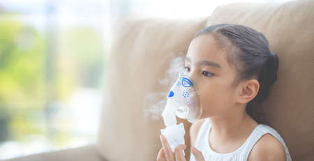 Cute Asian child  patient inhalation therapy by the mask of inhaler with soft stream smoke from bronchodilator.